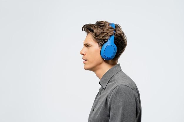 Ritratto di un giovane ragazzo in abito grigio in piedi lateralmente ascoltando musica che indossa le cuffie senza fili blu Foto Premium