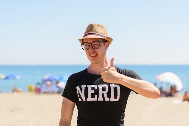 Ritratto di giovane turista bello come nerd in spiaggia in spagna Foto Premium