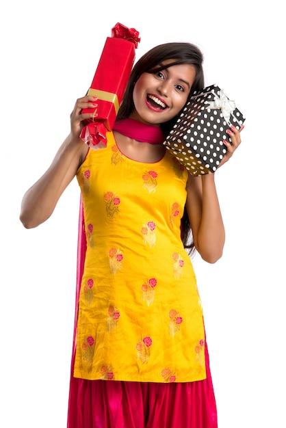 Ritratto di giovane ragazza indiana sorridente felice che tiene i contenitori di regalo su uno spazio bianco. Foto Premium