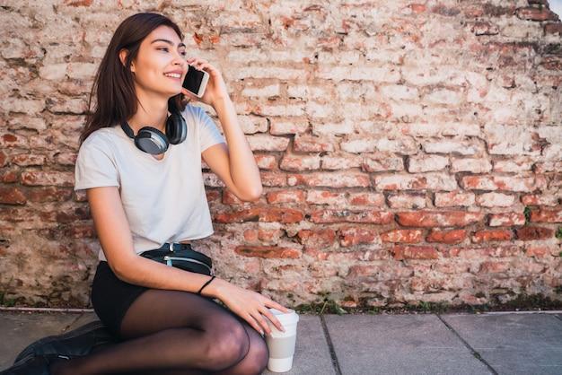 Ritratto di giovane donna latina parla al telefono mentre è seduto all'aperto contro il muro di mattoni. concetto urbano. Foto Premium