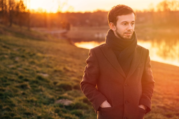 Ritratto di un giovane uomo in un cappotto che cammina nel bosco. giovane che cammina nella foresta giornata di sole primaverile. Foto Premium