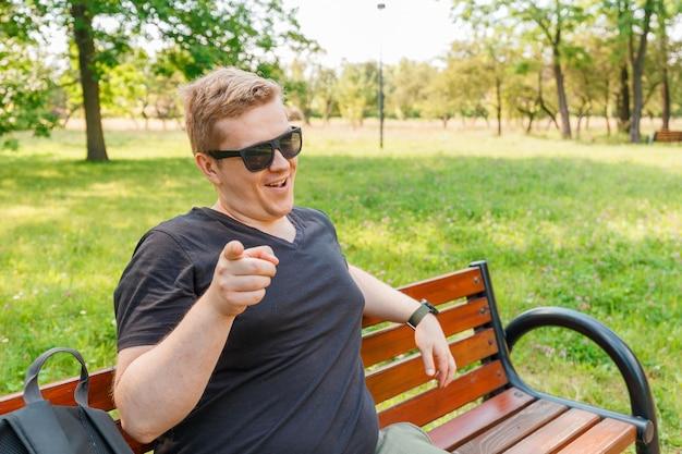 Ritratto di un giovane uomo nel parco. espressione facciale di emozione. sorriso, sentimenti e reazione delle persone. sorriso psicopatico omicida. Foto Premium