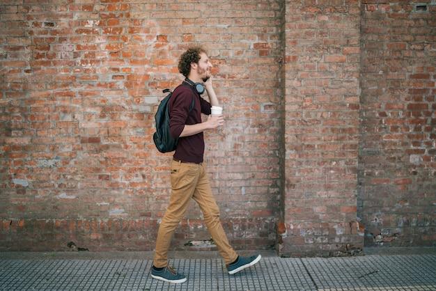 Ritratto di giovane uomo che parla al telefono mentre si cammina all'aperto in strada. comunicazione e concetto urbano. Foto Premium