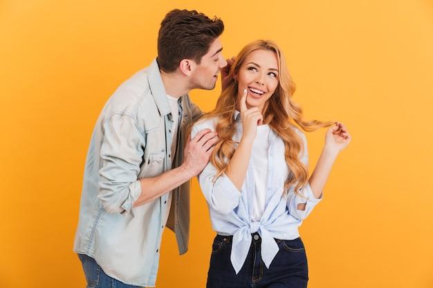 Ritratto di giovane uomo che bisbiglia pettegolezzi segreti o interessanti alla donna curiosa nel suo orecchio, isolato sopra la parete gialla Foto Premium