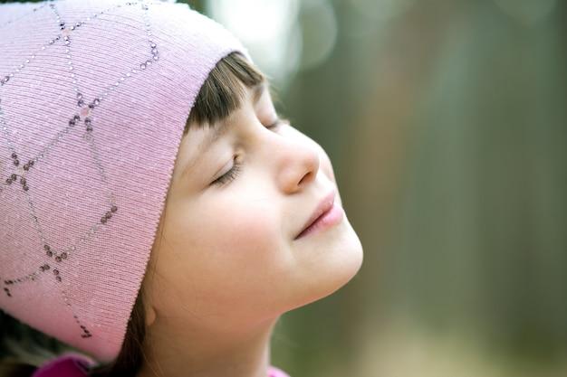 Ritratto di giovane ragazza graziosa del bambino che indossa giacca rosa e cappuccio godendo calda giornata di sole in primavera all'aperto. Foto Premium