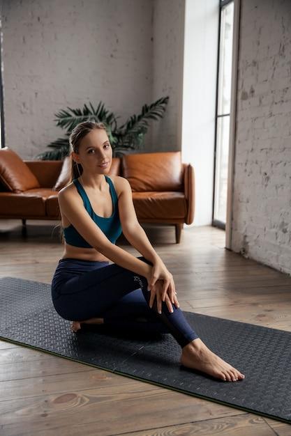 Ritratto di giovane donna sportiva a praticare yoga e stretching del corpo a casa. foto di alta qualità Foto Premium