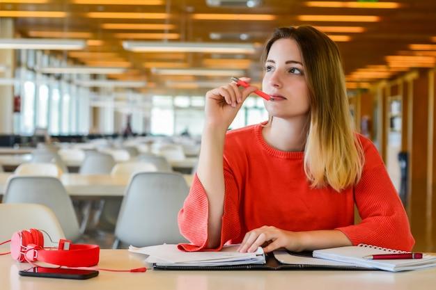 Ritratto di giovane studente che studia presso la biblioteca universitaria. concetto di educazione e stile di vita. Foto Premium