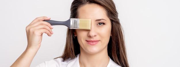 Ritratto di giovane donna che nasconde il suo occhio con il pennello sul muro bianco Foto Premium