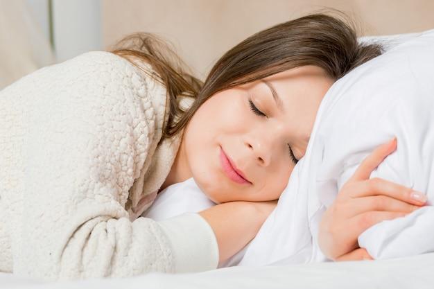 Ritratto di una giovane donna che dorme sul letto a casa Foto Premium