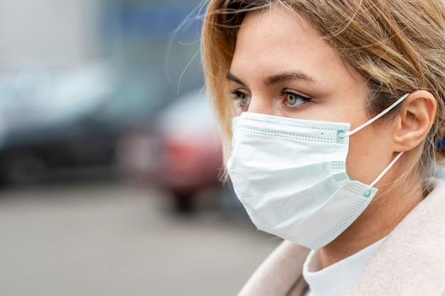 Ritratto di giovane donna che indossa una maschera chirurgica Foto Premium