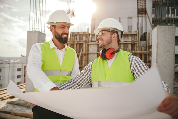 Uomini adulti positivi che leggono il progetto durante i lavori di costruzione Foto Premium