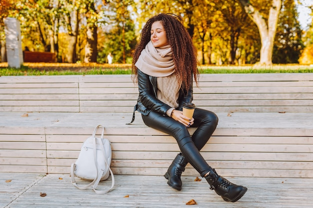 Positivo womansit capelli afro sulla panchina nel parco di autunno in una giornata di sole con caffè e respirando profondamente Foto Premium