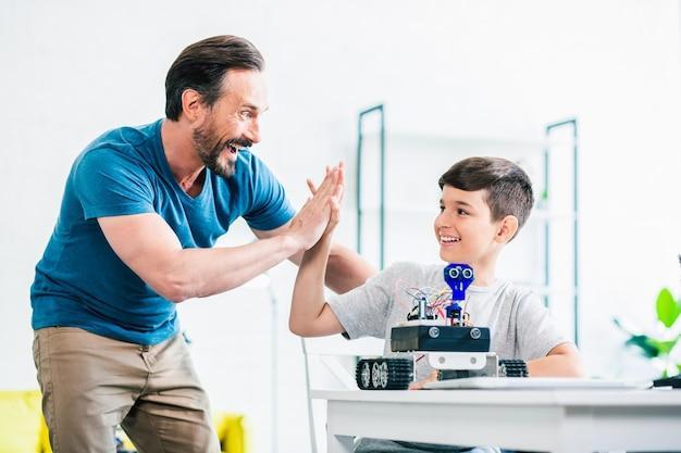 Padre felice e positivo che dà il cinque a suo figlio mentre finisce il loro progetto di ingegneria su un robot moderno Foto Premium