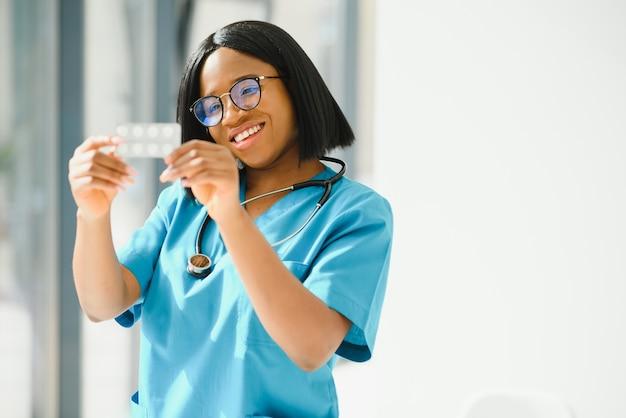 Positivo gioioso giovane donna afro-americana farmacista o medico, tenendo in mano le pillole Foto Premium