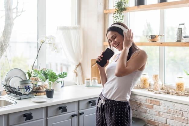Giovane donna positiva che ascolta la musica Foto Premium