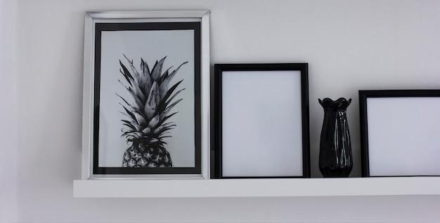 Manifesti con ananas e cornici pulite sullo scaffale, interni moderni in bianco e nero, banner Foto Premium