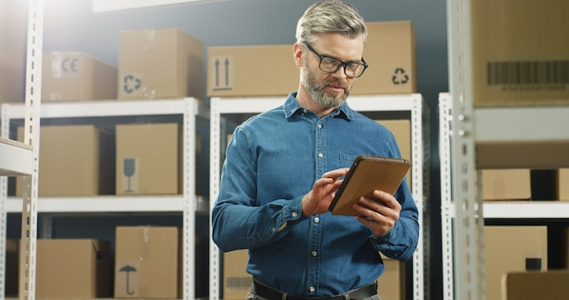 Postino in bicchieri in piedi nel negozio postale con pacchi e toccando sul tablet pc. lavoratore maschio con il computer che fa registrazione nella sala parto piena di scatole. Foto Premium