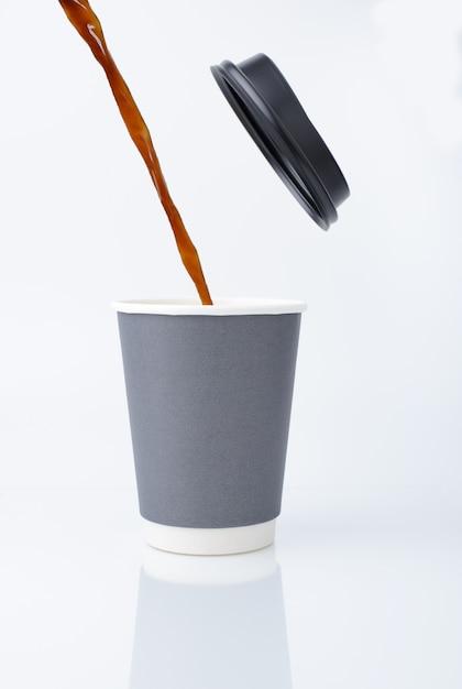 Versare l'acqua del caffè in un bicchiere di carta con coperchio. Foto Premium