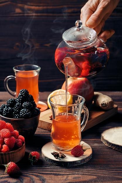 Versare frutta e tisane appena preparate dal bollitore nella tazza Foto Premium