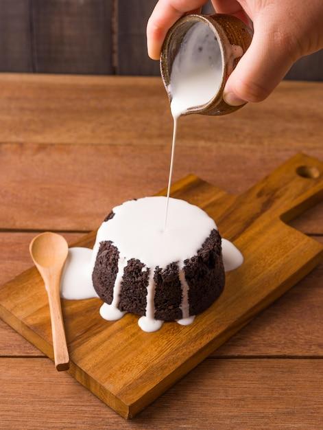Versando la salsa di latte sui brownie al cioccolato sul piatto di legno e sullo sfondo di legno. prodotti da forno e dolci fatti in casa Foto Premium