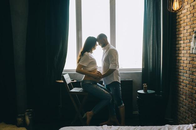 Concetto della gente e di gravidanza - uomo felice che abbraccia la sua moglie incinta che sta alla finestra a casa Foto Premium
