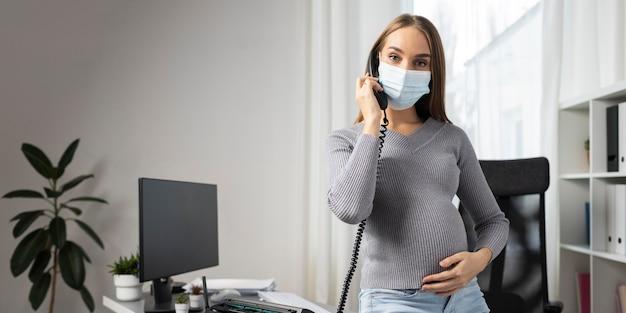 Imprenditrice incinta indossando maschera medica in ufficio e parlando al telefono Foto Premium