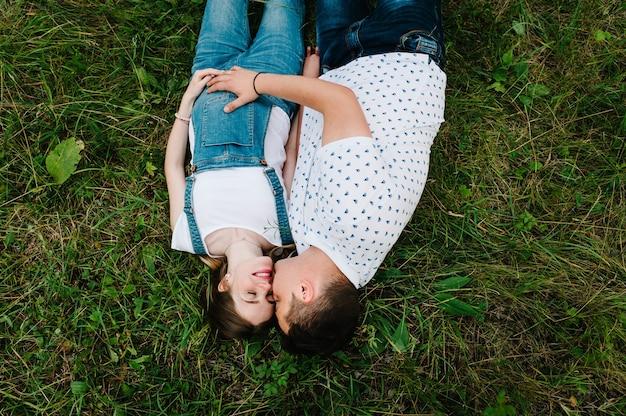 La ragazza incinta e suo marito sono felici di abbracciarsi, tenersi per mano, sulla pancia, sdraiarsi sull'erba all'aperto in giardino Foto Premium