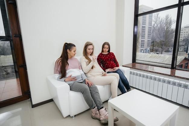 Le ragazze incinte si siedono sul divano e si divertono a chiacchierare tra loro. gravidanza e cura del futuro del bambino Foto Premium