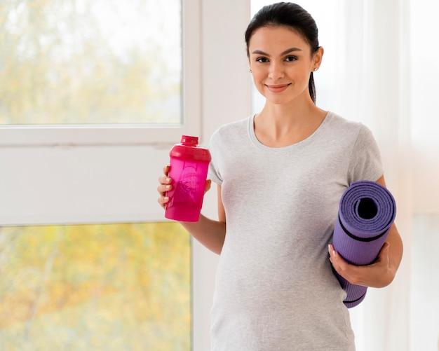 Donna incinta che tiene una stuoia di forma fisica e una bottiglia di acqua con lo spazio della copia Foto Premium