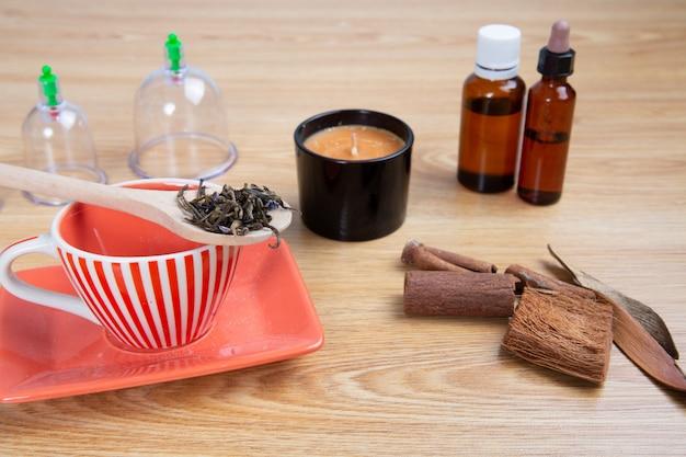 Preparazione per il tè zen con candela agli olii essenziali e massaggio con ventosa Foto Premium