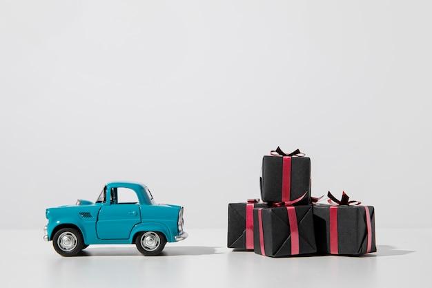 Scatole presenti e giocattolo auto blu Foto Premium