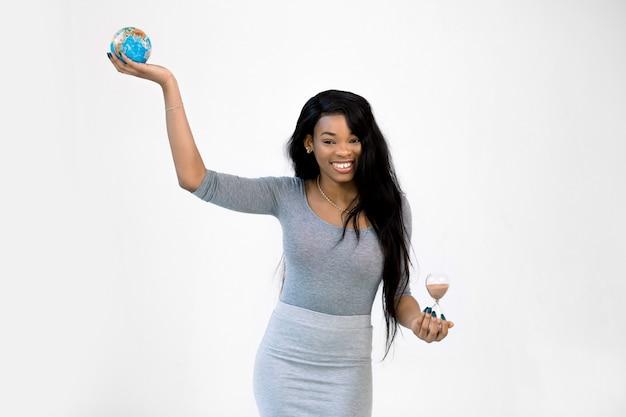 Ragazza abbastanza africana in vestito grigio che tiene il globo della terra in una mano e una clessidra in un'altra, sorridendo e controllando i precedenti bianchi Foto Premium