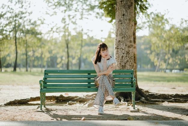La signora abbastanza asiatica in vestiti bianchi che si siedono con le sue gambe ha attraversato sul banco che si rilassa e che ascolta la musica dal suo telefono Foto Premium