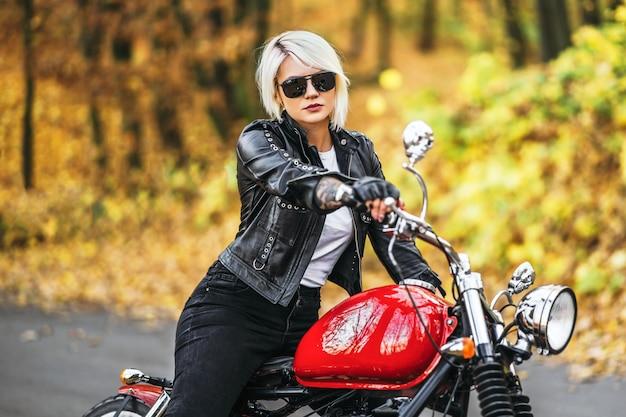Ragazza abbastanza bionda del motociclista che si siede vicino alla motocicletta rossa sulla strada nella foresta Foto Premium