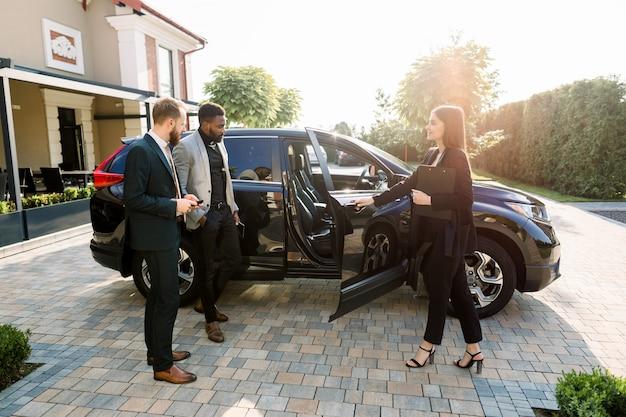 Bella commessa di auto in abiti d'affari aiutando i giovani due clienti multietnici di uomini d'affari a prendere una decisione mostrando una nuova auto, aprendo le porte della macchina, mentre si trovava sul cortile del salone dell'auto all'aperto Foto Premium