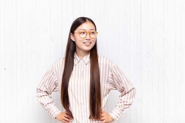 Bella donna cinese contro il muro bianco Foto Premium