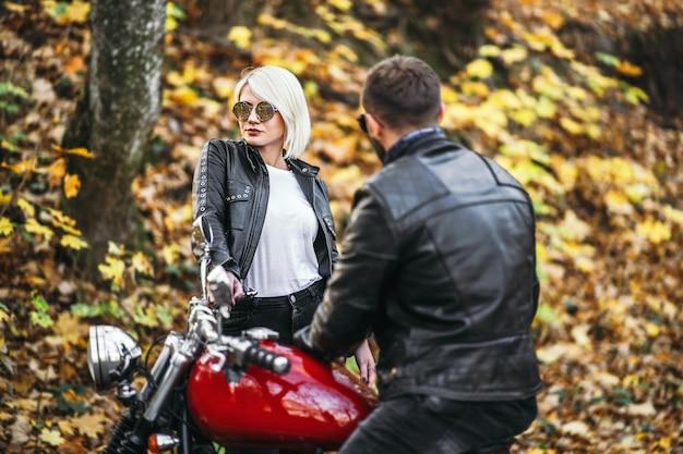 Bella coppia vicino alla moto rossa sulla strada nella foresta Foto Premium