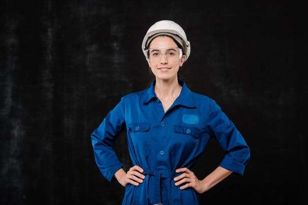 Piuttosto ingegnere in abiti da lavoro blu e occhiali protettivi e casco mantenendo le mani sulla vita su sfondo nero Foto Premium