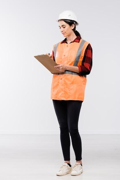 Costruttore abbastanza femminile in elmetto protettivo, flanella, leggins e giubbotto da lavoro che prende appunti nel documento davanti alla telecamera in isolamento Foto Premium
