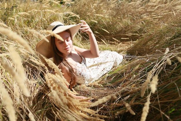 Bella ragazza che si distende all'aperto nel grano giallo dorato. stile boho moderno. Foto Premium