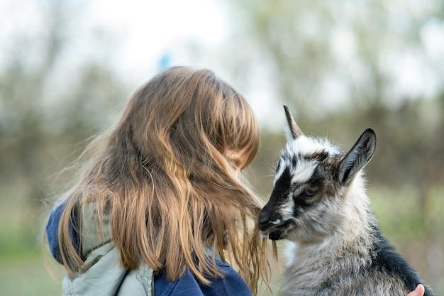 Ragazza abbastanza felice del bambino che gioca con la piccola capra del bambino al cortile dell'azienda agricola. Foto Premium