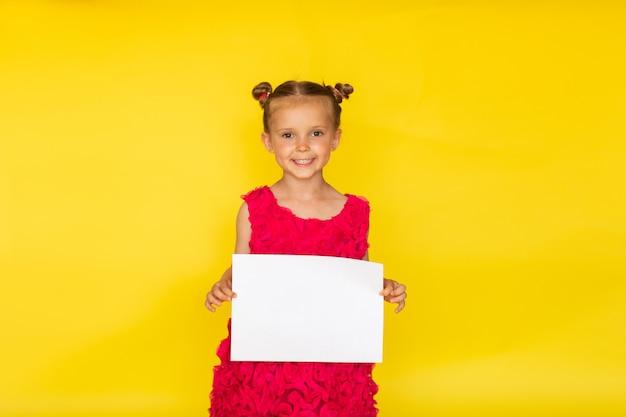 Abbastanza piccola ragazza a piedi nudi con due panini e in abito estivo rosa brillante in posa con la lista del libro bianco su sfondo giallo. copia spazio Foto Premium