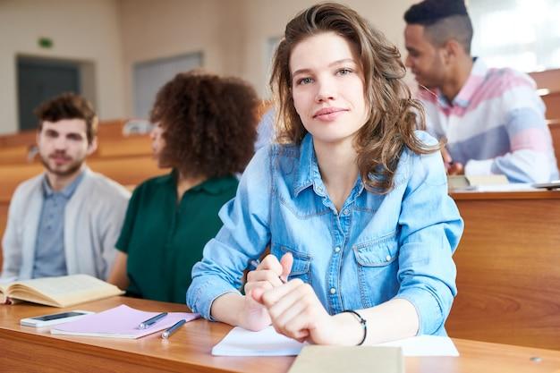 Ragazza graziosa dello studente alla classe universitaria Foto Premium