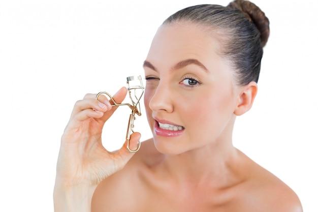 Bella donna che arriccia le sue ciglia Foto Premium