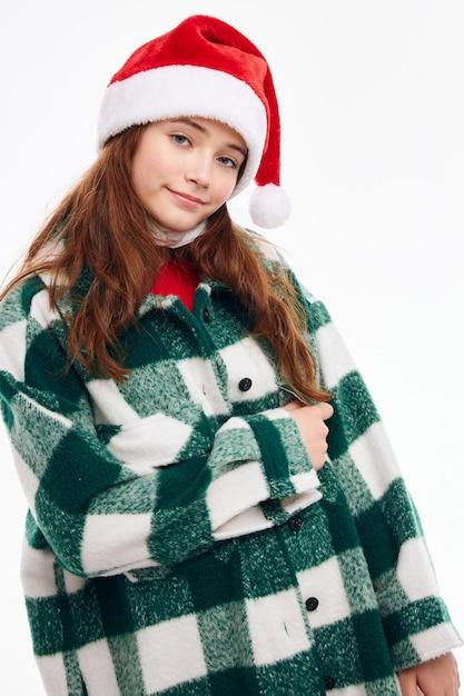 Bella donna che indossa santa cappello plaid cappotto vacanza divertente studio Foto Premium