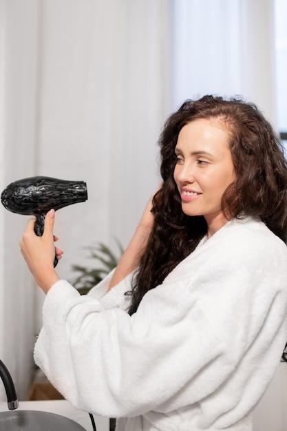 Piuttosto giovane donna sorridente con asciugacapelli prendersi cura dei suoi lunghi capelli ondulati scuri dopo averlo lavato in bagno Foto Premium