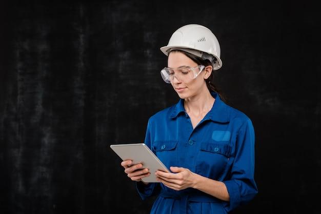 Tecnico abbastanza giovane in elmetto protettivo e abbigliamento da lavoro blu che guarda lo schermo del touchpad durante la navigazione in rete in isolamento Foto Premium
