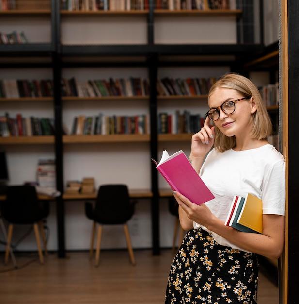 Bella giovane donna in posa in biblioteca Foto Premium