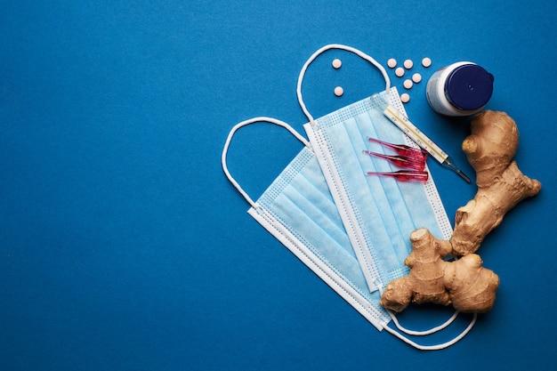 Prevenire il coronavirus. maschera medica, termometro, vitamine, siringa su sfondo blu. Foto Premium