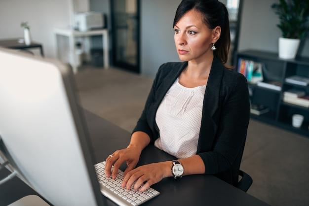 Problemi in azienda. donna di affari seria che digita sulla tastiera. Foto Premium